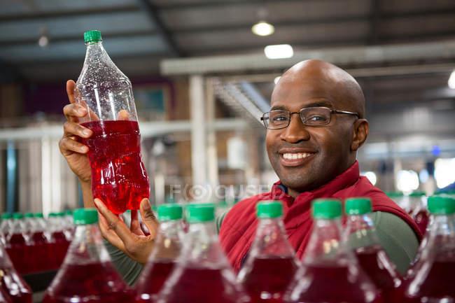 Retrato del trabajador masculino sonriente mostrando la botella de jugo en fábrica - foto de stock