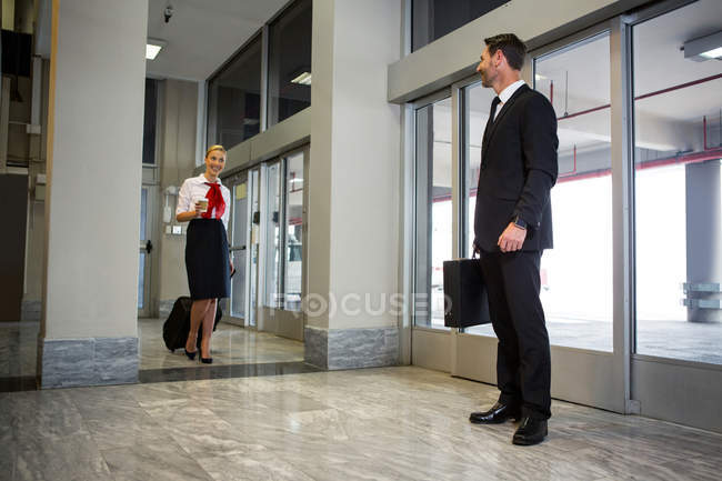 Female staff interacting with businessman in the airport terminal — Stock Photo
