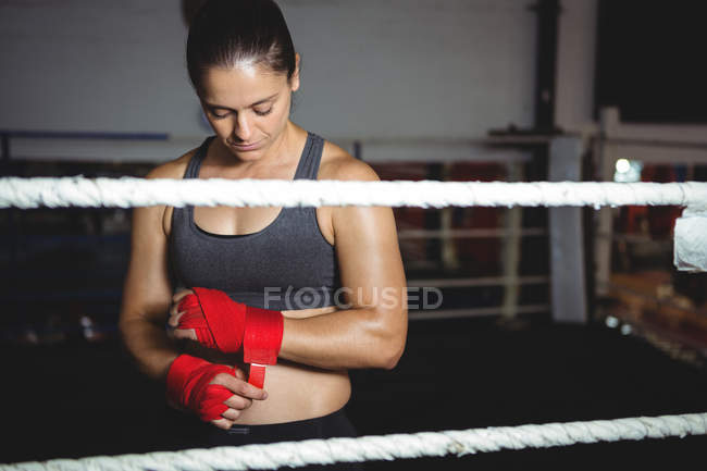 Female boxer wearing red strap on wrist in fitness studio — Stock Photo