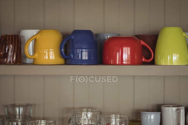 Gros plan de tasses colorées sur l'étagère de la cuisine — Photo de stock