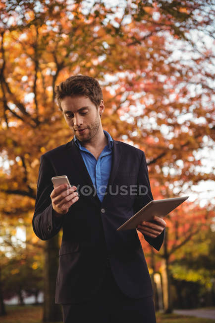 Businessman using mobile phone and holding digital tablet in autumn — Stock Photo