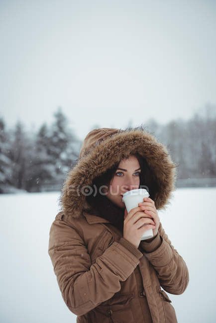 Beautiful woman in fur jacket having coffee during winter — Stock Photo
