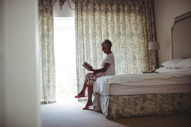Senior mujer sentada en la cama y lectura en camas - foto de stock