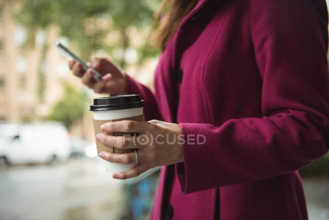 Mid section of businesswoman holding disposable coffee cup and using mobile phone on street — Stock Photo