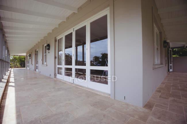 Exterior de uma casa com varanda vazia com windows — Fotografia de Stock