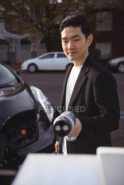 Smiling man holding car charger at electric vehicle charging station — Stock Photo