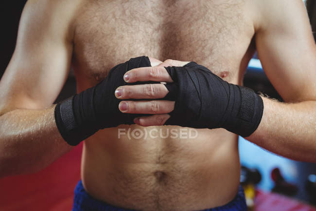 Mid section of boxer wearing black strap on wrists in fitness studio — Stock Photo