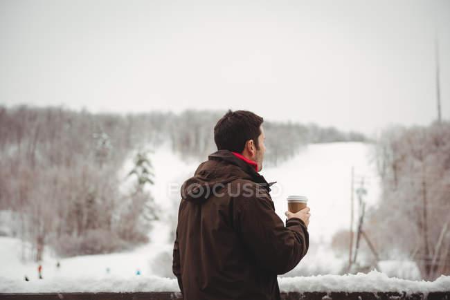 Uomo che beve caffè sul balcone godendo della vista — Foto stock