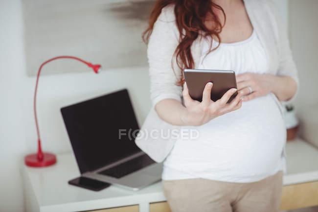 Средняя часть беременной женщины с помощью цифрового планшета в кабинете дома — стоковое фото