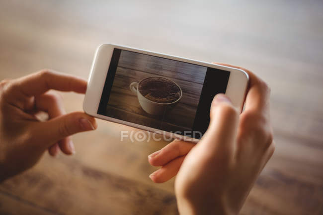 Woman clicking photo of coffee cup in cafe — Stock Photo