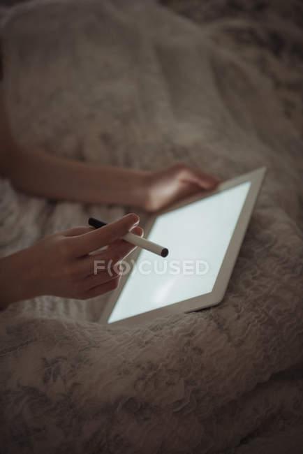 Крупный план женщины с использованием цифрового планшета в постели — стоковое фото