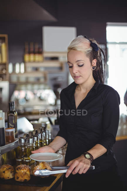 Waitress serving muffin in a plate at counter in cafe — Stock Photo
