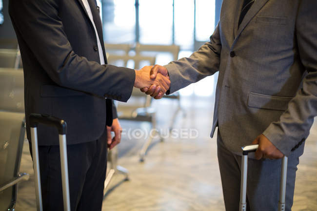 Mid-section of business people shaking hand in waiting area with airport — Stock Photo