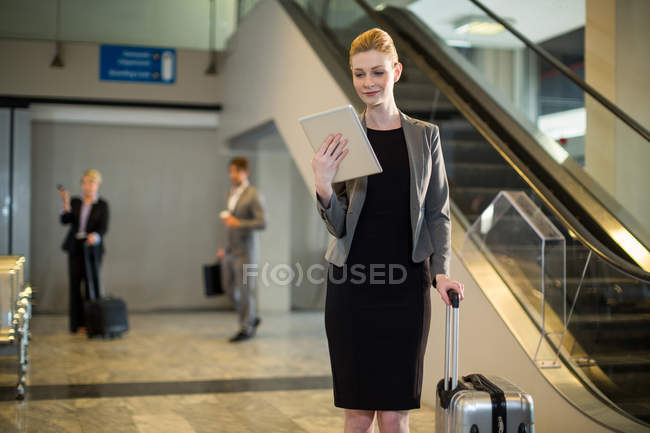 Businesswoman using digital tablet at airport — Stock Photo