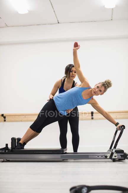 Allenatrice assistere donna con stretching esercizio il riformatore in palestra — Foto stock