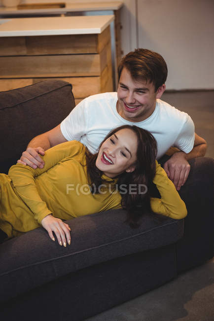 Cheerful couple lying together on sofa in living room at home — Stock Photo