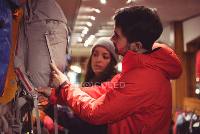 Couple selecting backpack together in a shop — Stock Photo