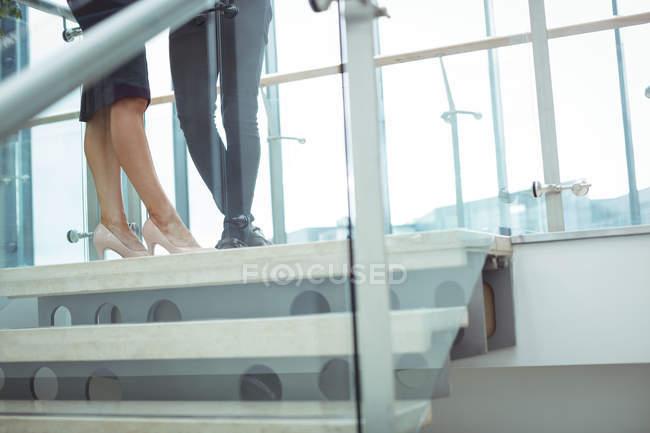 Faible section des dirigeants d'entreprise debout près de l'escalier dans le couloir de bureau — Photo de stock