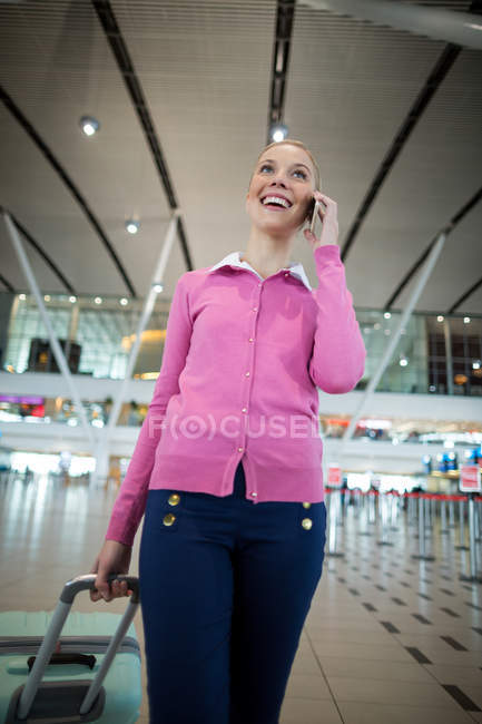 Female commuter with luggage talking on mobile phone in airport — Stock Photo