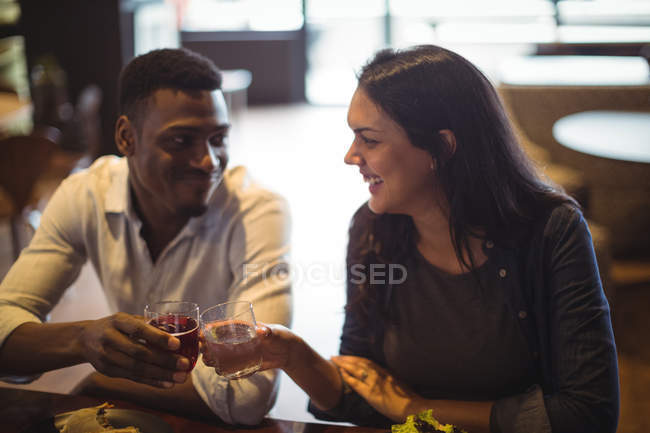 Couple toasting glasses of drink in restaurant — Stock Photo