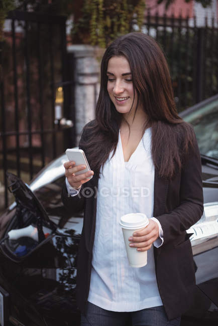 Woman using mobile phone while car being charged in background at electric vehicle charging station — Stock Photo