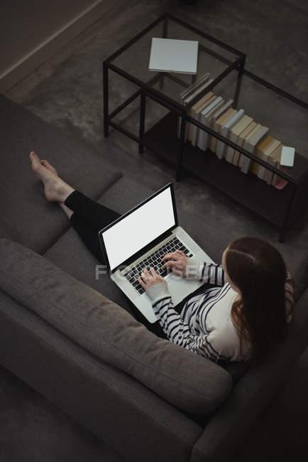 Vista ad alto angolo della donna che utilizza il computer portatile sul divano in soggiorno — Foto stock
