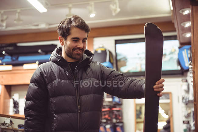 Handsome man selecting ski in a shop — Stock Photo