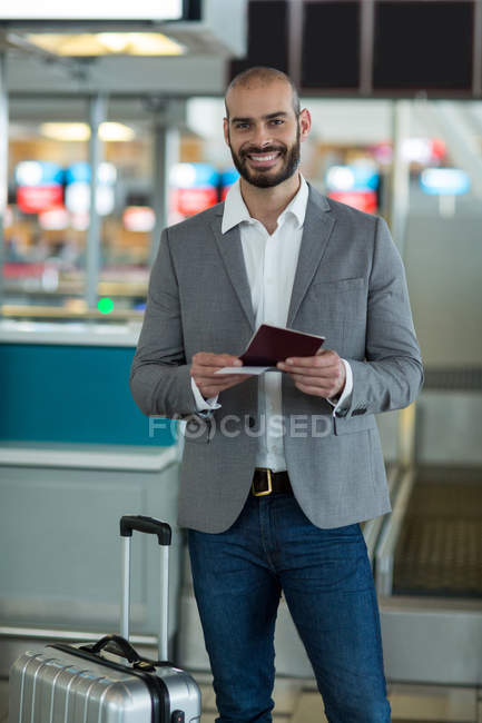 Portrait of smiling businessman with luggage checking his boarding pass at airport terminal — Stock Photo