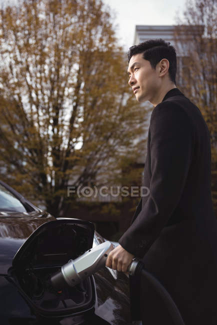 Homme confiant recharge voiture électrique à la station de recharge de véhicule électrique — Photo de stock