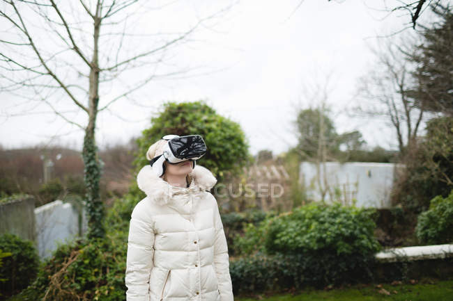 Woman in fury coat using virtual reality headset outdoors — Stock Photo