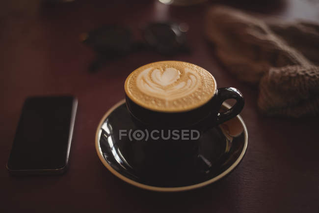 Cup of coffee with smartphone on wood table — Stock Photo