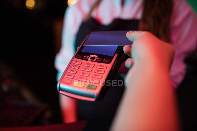 Customer making payment through credit card at counter in bar — Stock Photo