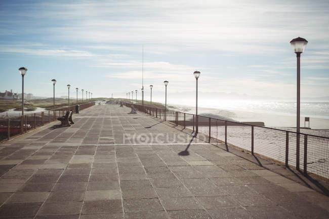 Spiaggia vuota molo con lampioni alla luce del sole — Foto stock