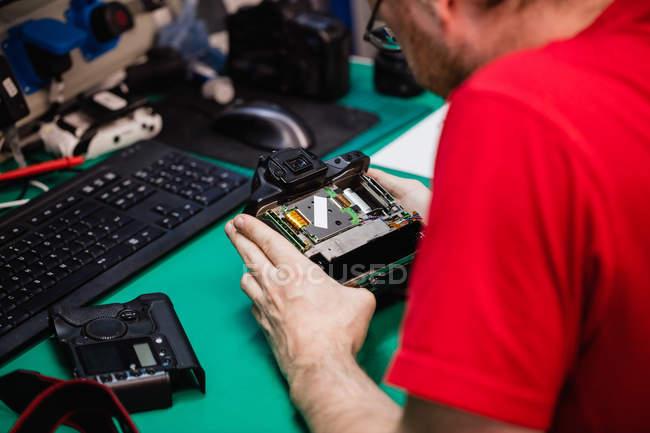 Man repairing digital camera in repair shop — Stock Photo