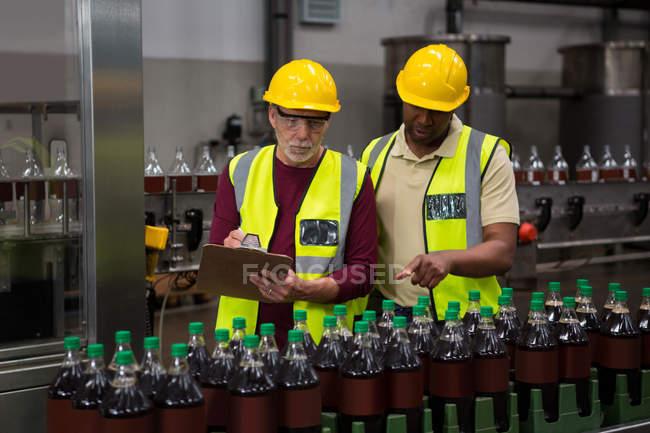 Мужчины обсуждают на соковом заводе — стоковое фото