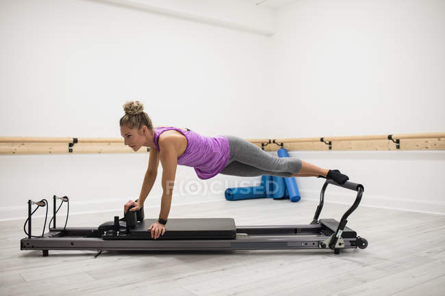 Woman in pink sportswear exercising on reformer in gym — Stock Photo