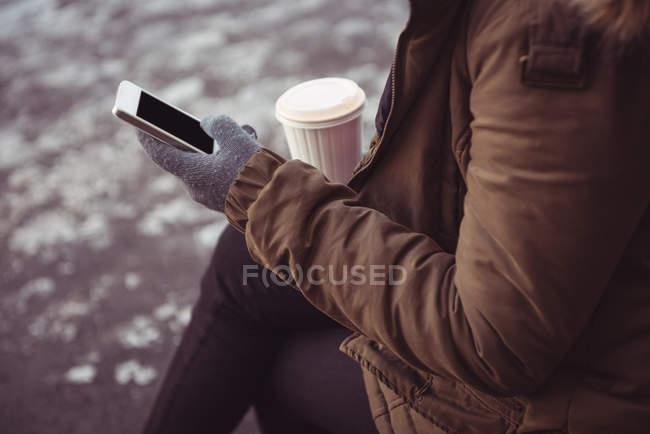 Mittleren Bereich der Frau mit Handy am Flussufer im winter — Stockfoto