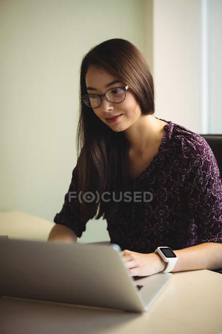 Empresária em óculos trabalhando no laptop no escritório — Fotografia de Stock