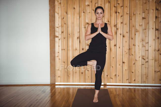 Frau in Baumpose beim Yoga im Fitnessstudio — Stockfoto