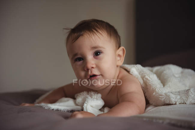 Cute baby lying on front in bedroom at home — Stock Photo