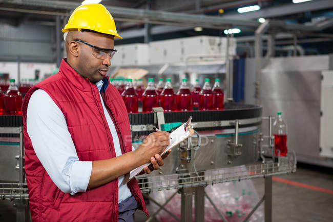 Serious male employee noting about products in juice factory - foto de stock