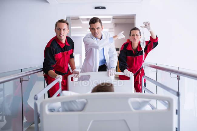 Médicos empurrando cama de maca de emergência no corredor do hospital — Fotografia de Stock