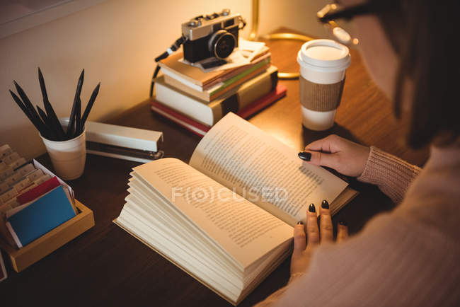 Woman reading book while having coffee in living room at home — Stock Photo