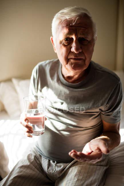 Hombre mayor tomando medicina en el dormitorio en casa - foto de stock