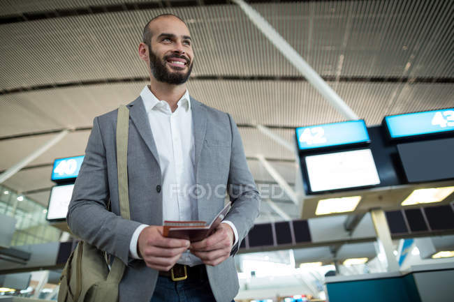 Smiling businessman holding a boarding pass and passport at airport terminal - foto de stock