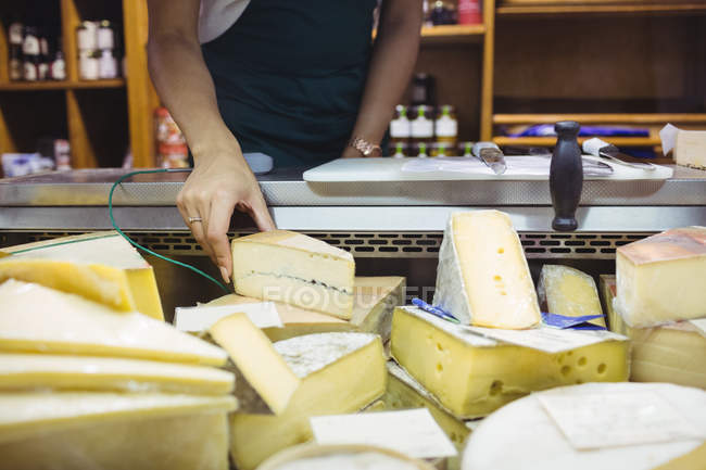 Mid section of female staff working at cheese counter in supermarket — Stock Photo