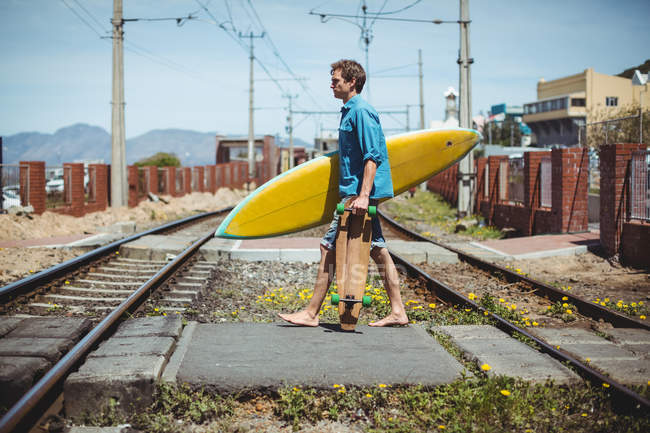 Man carrying skateboard and surfboard while crossing railway track — Stock Photo