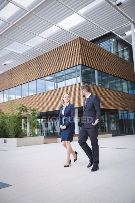 Businessman walking with colleague outside the entrance of an office building — Stock Photo