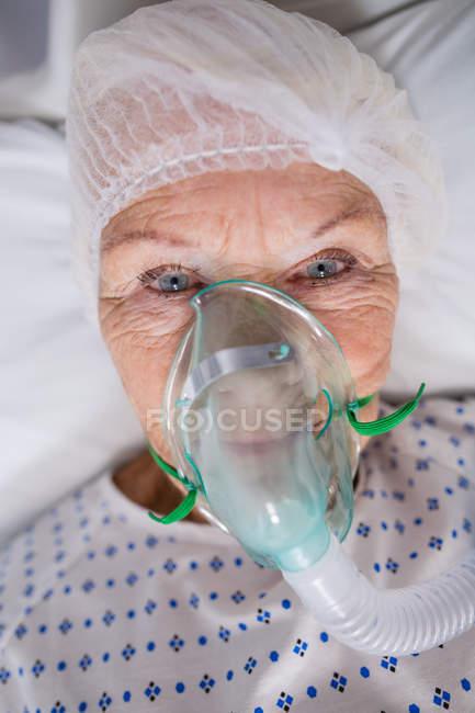 Primo piano del paziente anziano che indossa una maschera di ossigeno sdraiato sul letto d'ospedale — Foto stock