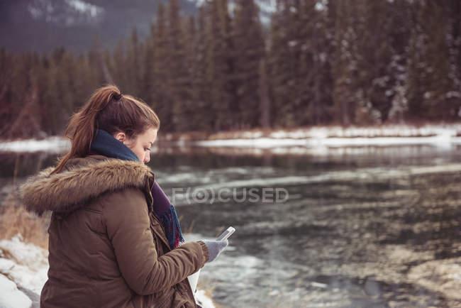 Frau sitzt am Ufer und mit Handy im winter — Stockfoto